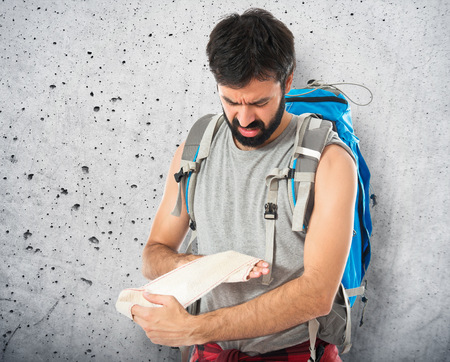 wounded: Backpacker healing a wounded over white background