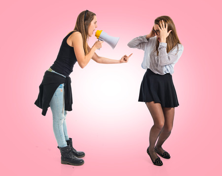 preppy: Girl shouting at her sister by megaphone Stock Photo