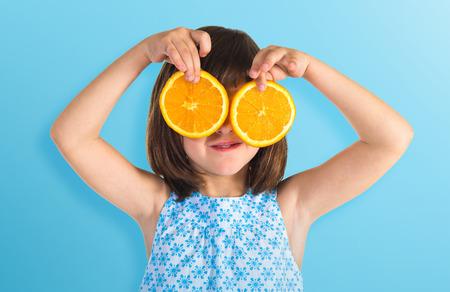 Meisje die stukjes sinaasappel een bril Stockfoto