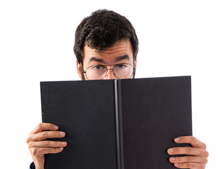Vintage young man hiding behind a book