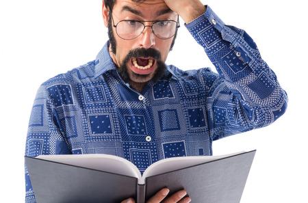 sorprendido: Joven libro de lectura del hombre Sorprendido Foto de archivo