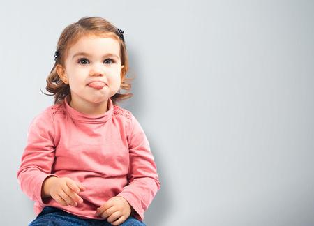 sticking out tongue: Linda ni�a sacar la lengua sobre fondo gris Foto de archivo