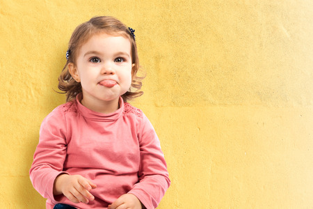 cute babies: Cute baby girl sticking out tongue over yellow background