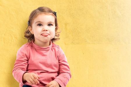 bebes lindos: Linda niña sacar la lengua sobre fondo amarillo