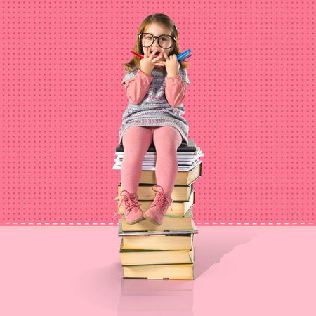 mignonne petite fille: Surpris petite fille avec des lunettes assis sur les livres Banque d'images