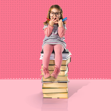 sit studio: Surprised little girl with glasses sitting on books