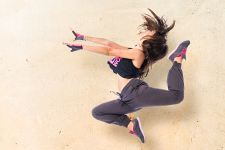 Teenager girl jumping in hip hop style Archivio Fotografico