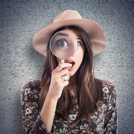 Surprised woman with magnifying glass