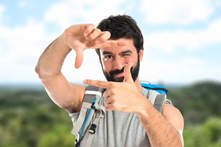 square shape: backpacker focusing with his fingers on a white background