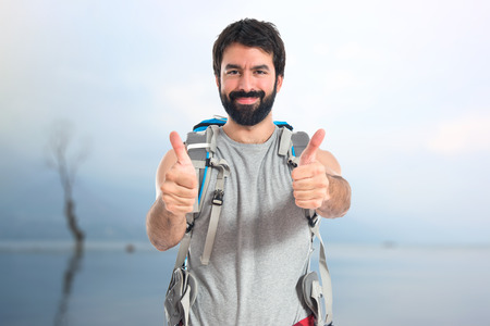 backpacker: Backpacker with thumb up over white background