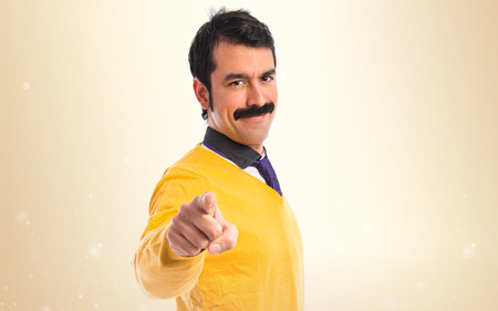 Man with moustache pointing to the front
