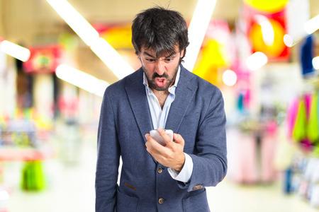 jefe enojado: El hombre enojado hablando con móvil sobre el fondo blanco Foto de archivo