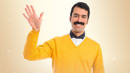 goodbye: Man with moustache saluting over white background