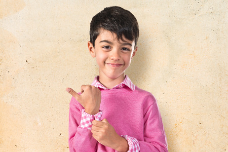 cool backgrounds: Portratit of young boy with pink sweater Stock Photo