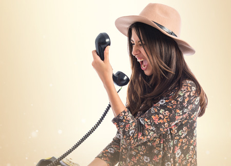 Angry woman talking to vintage phone