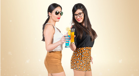 liquor girl: Twin sisters with colorful drinks Stock Photo