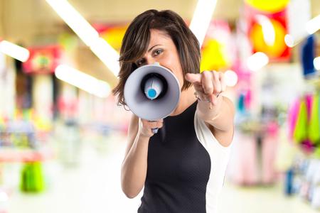 Mooi meisje schreeuwen met een megafoon op een witte achtergrond