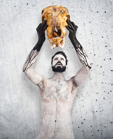 satanism: Primitive man offering veal skull Stock Photo