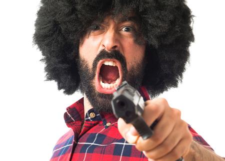hombre disparando: Afro man shooting with a pistol Foto de archivo