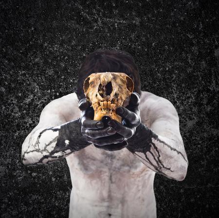 satanism: Primitive man offering a rabbit skull