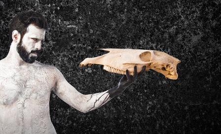 hombre prehistorico: hombre prehistórico en busca de cráneo de caballo Foto de archivo
