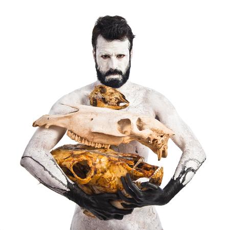 hombre prehistorico: prehistóricos hombre que sostiene cráneos de animales Foto de archivo