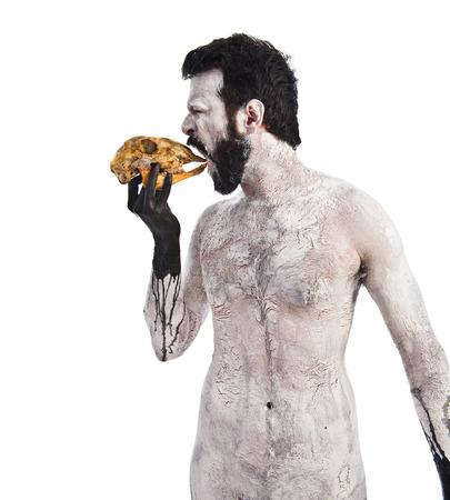 satanism: Primitive man eating a rabbit skull