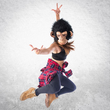 hip hop style: Woman with monkey mask jumping in hip hop style Stock Photo