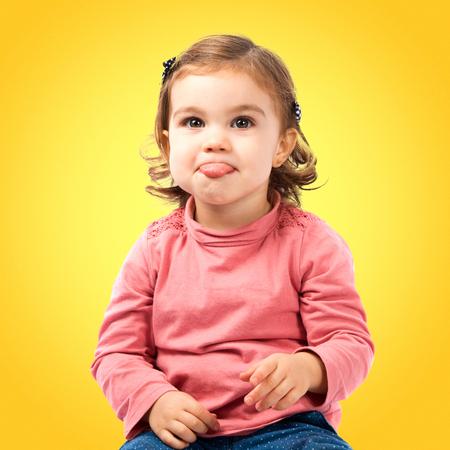 sacar la lengua: Linda niña sacar la lengua sobre el fondo blanco