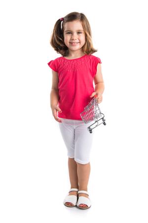 chicas de compras: Niña jugando con un mini carro de supermaeket Foto de archivo