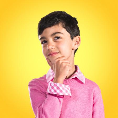 pensando: Kid pensamiento sobre fondo blanco Foto de archivo