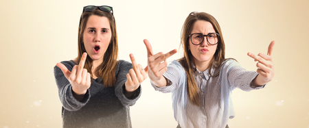 family isolated: Twin sisters making horn gesture