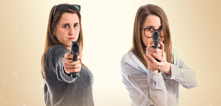 preppy: Twin sisters shooting with a pistol