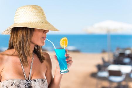 liquor girl: Woman in bikini drinking a cocktail