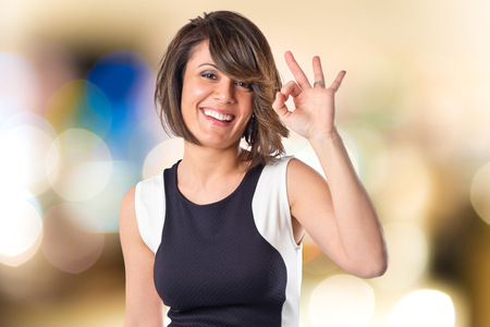 ok sign: Pretty woman making Ok sign over white background Stock Photo