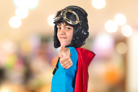 Child dressed like superhero with thumbs up