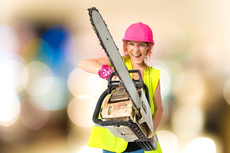 mujer trabajadora: Worker woman with chainsaw over white background Foto de archivo
