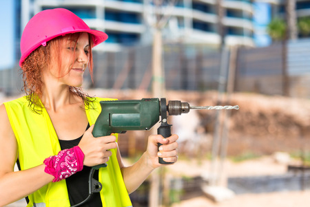 mujer trabajadora: Worker woman with drill over white background