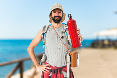 man drinking water: Backpacker drinking water over white background