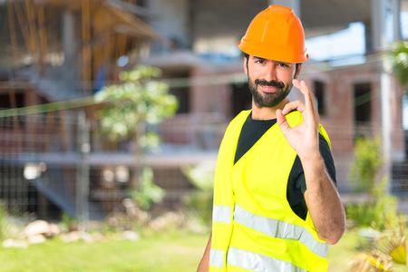 constructor: Trabajador que hace la muestra Ok sobre fondo blanco Foto de archivo