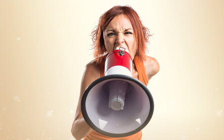 woman shouting: Woman shouting by megaphone Stock Photo