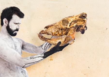prehistoric man: prehistoric man looking veal skull Stock Photo