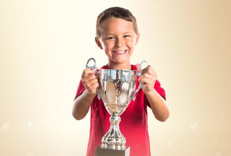 Kid holding a trophy Standard-Bild