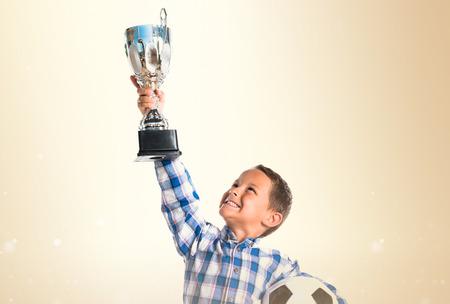 football trophy: Kid holding a football trophy