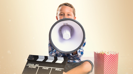 Kid with clapperboard and popcorns shouting by megaphone Stock Photo