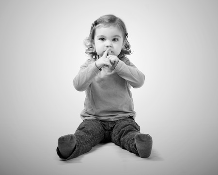 Cute girl doing silence gesture over white background Stock Photo