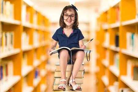 estudiando: Muchacha que estudia en una pila de libros