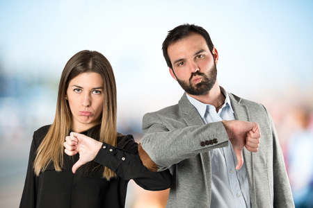 THUMBS DOWN: Couple with their thumbs down over white background Stock Photo