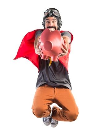 Superhero holding a piggybank