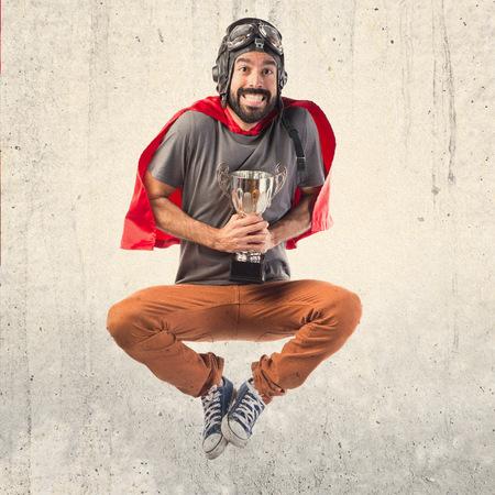 hombre rojo: Superhero sostiene un trofeo Foto de archivo